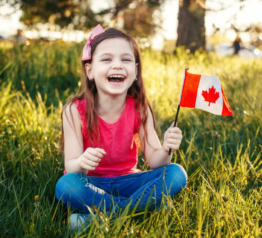 Adorable Cute Happy Caucasian Girl Holding Canadian Flag. Smilin